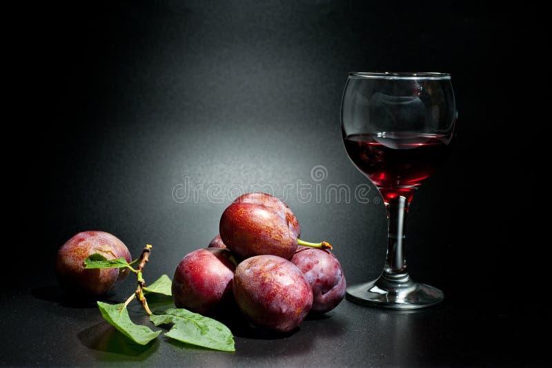 Pruimen rijp en sappig geschoten close-up op een donkere achtergrond en een glas wijn stock fotografie