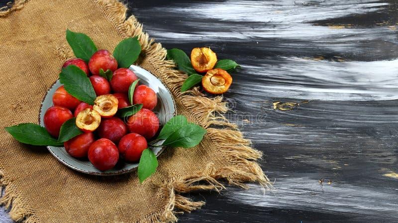 pruimen rode zoete pruimen met groene bladeren op een ronde plaat en oude doek op een donkere achtergrond Vlak leg, ruimte voor t royalty-vrije stock foto