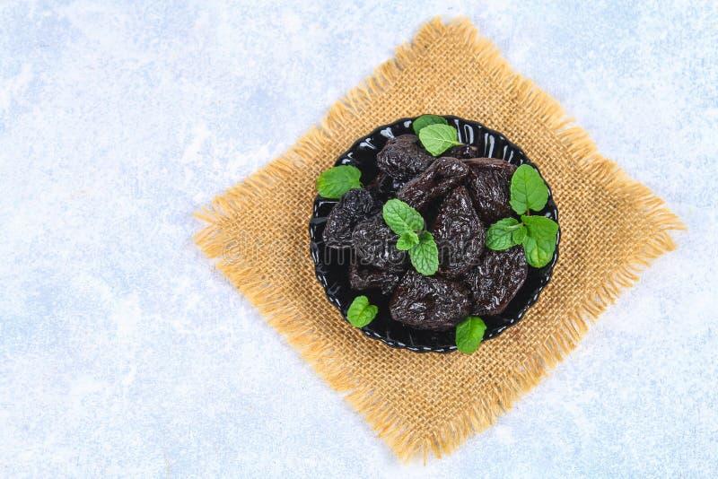 Pruneaux et feuilles en bon état fraîches dans une cuvette sur une table concrète photographie stock