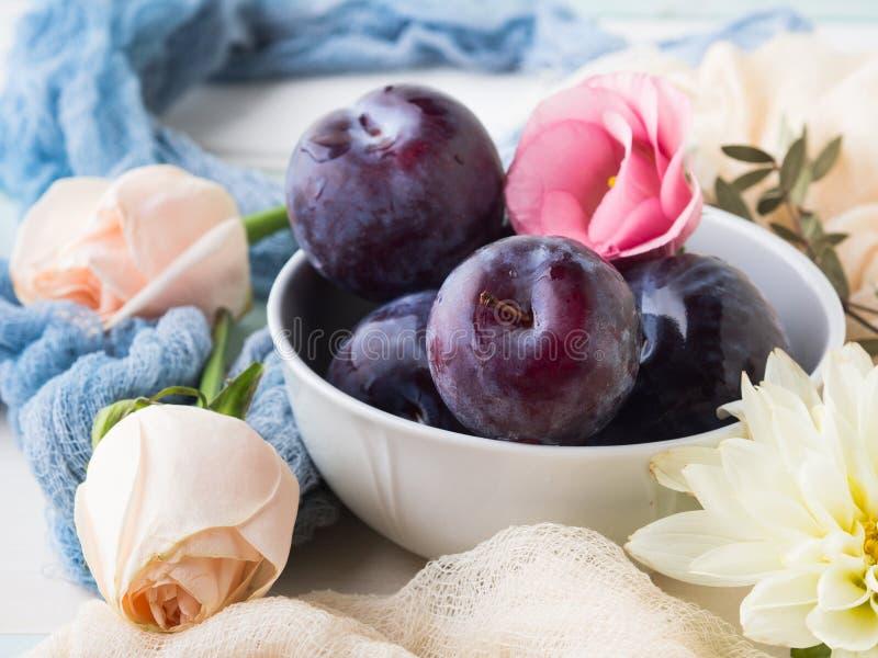 Prunes bleues dans la cuvette avec des fleurs images libres de droits