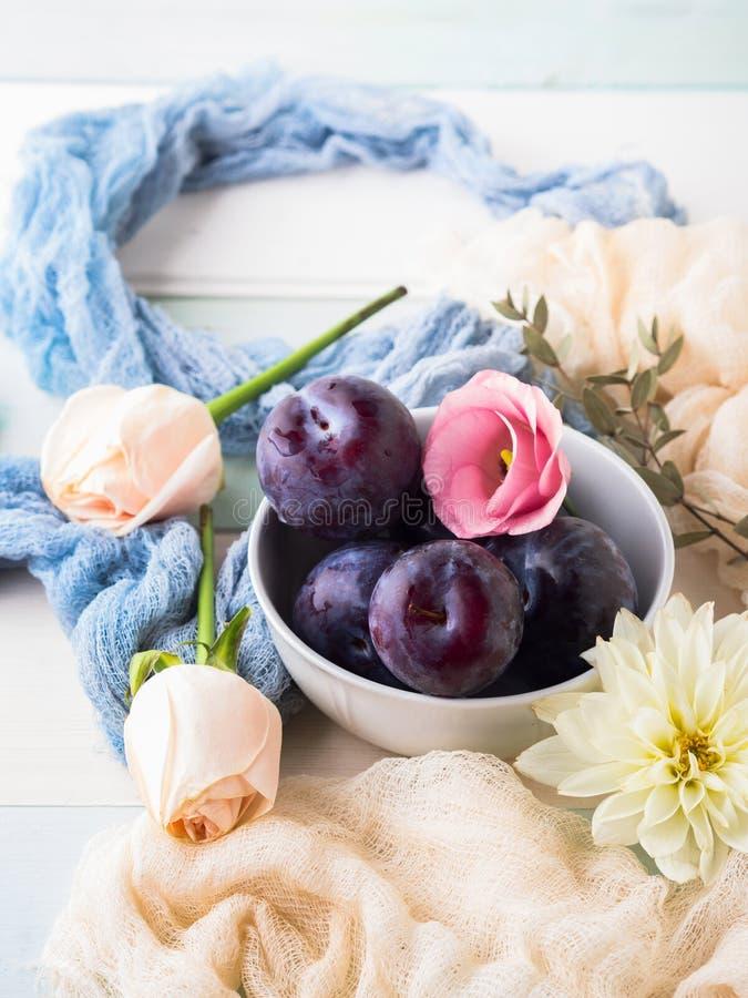 Prunes bleues dans la cuvette avec des fleurs photo stock