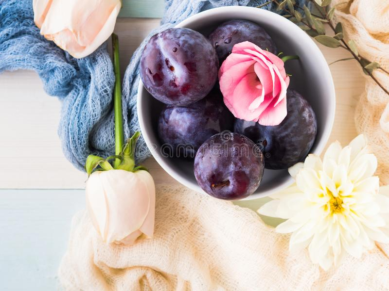 Prunes bleues dans la cuvette avec des fleurs photographie stock