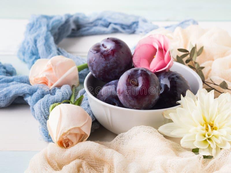 Prunes bleues dans la cuvette avec des fleurs photos libres de droits