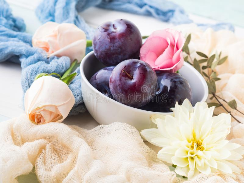 Prunes bleues dans la cuvette avec des fleurs image stock