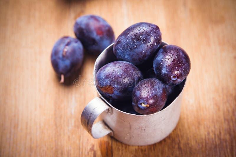 Prunes bleues dans la tasse photos stock