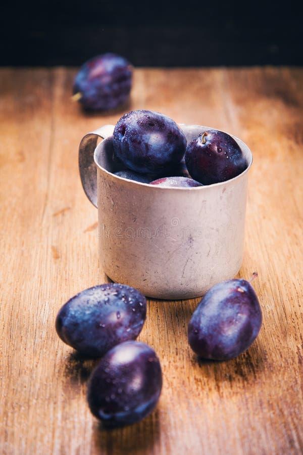 Prunes bleues dans la tasse images stock
