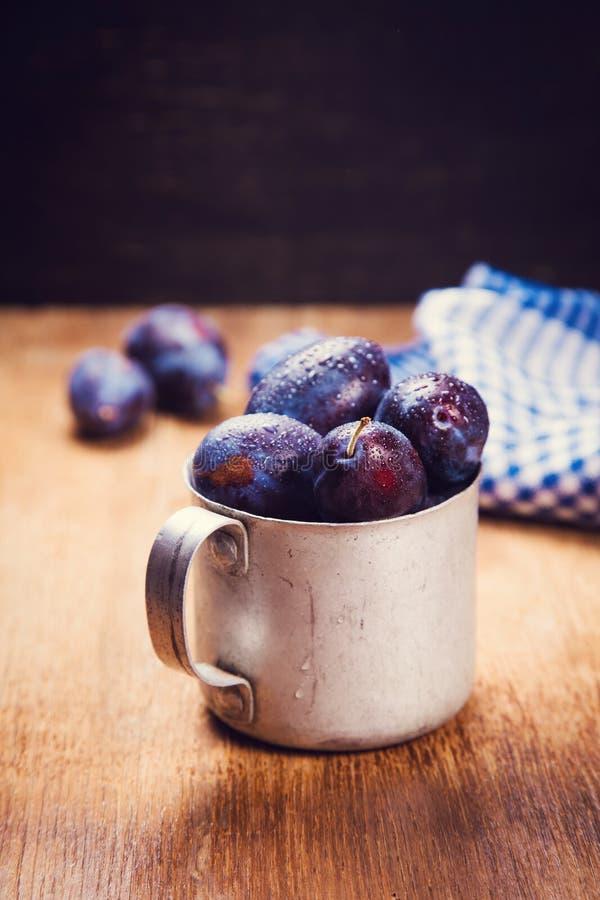 Prunes bleues dans la tasse image libre de droits