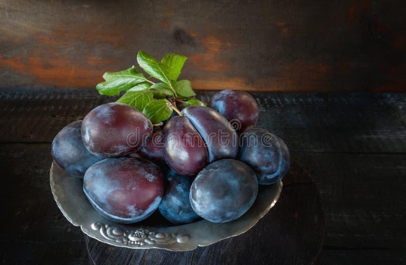Prunes bleues mûres et juteuses dans un panier en osier dans un style rustique Action de grâces heureuse Copiez l'espace image stock
