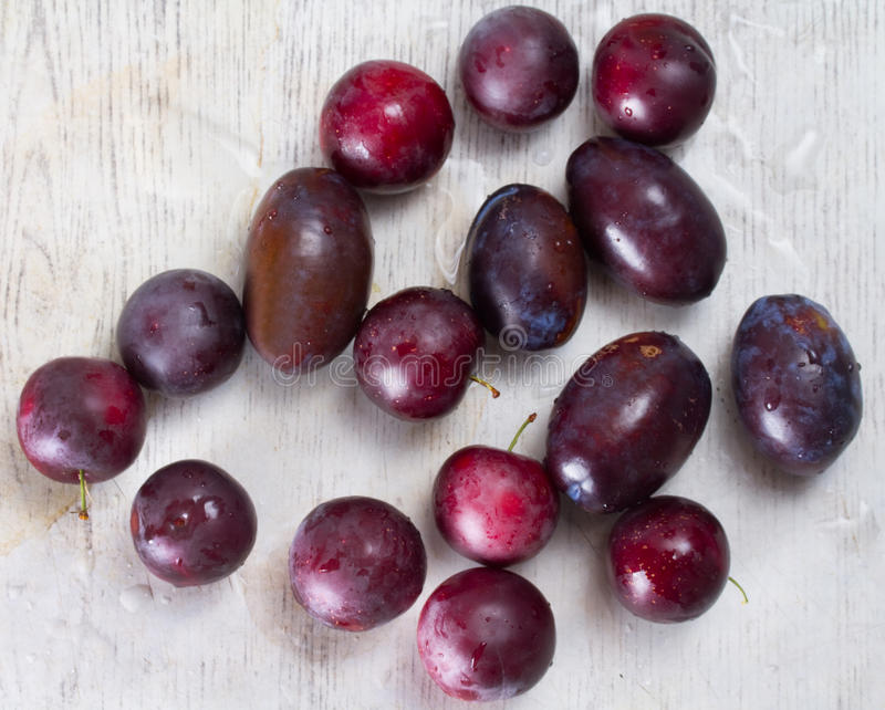 Prunes et cerise-prune mûres sur une table photo stock