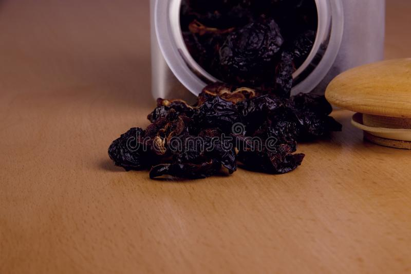 Prunes in a glass jar. Prunes spilled from a jar on the table stock photos