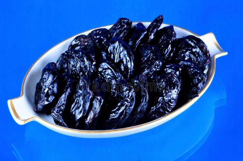 Prunes, healthy food — plum in dried form,dried fruit, on a blue background. In cooking prunes — sweet dessert, compote and royalty free stock images