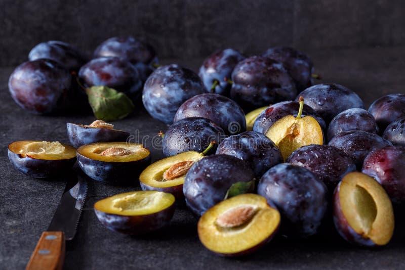 Prunes juteuses fraîches bleues sur la table foncée photos stock