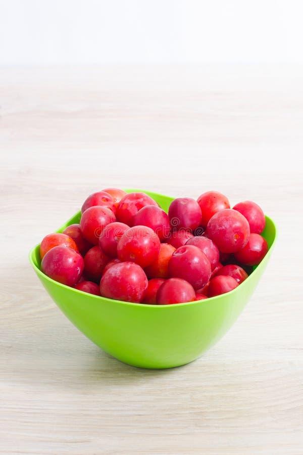 Prunes rouges lavées dans le plat vert sur une table légère image libre de droits