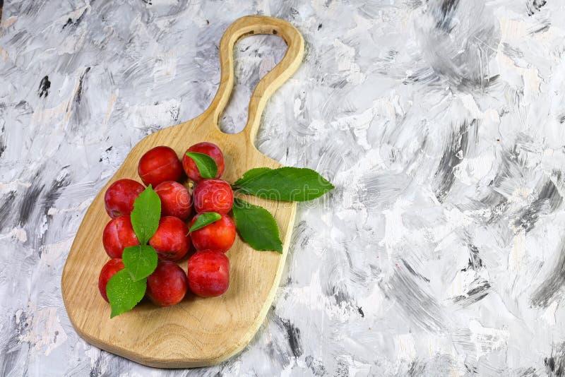 Prunes rouges mûres avec des feuilles sur un conseil en bois sur un fond clair, image authentique de mode de vie Produit local de photographie stock libre de droits