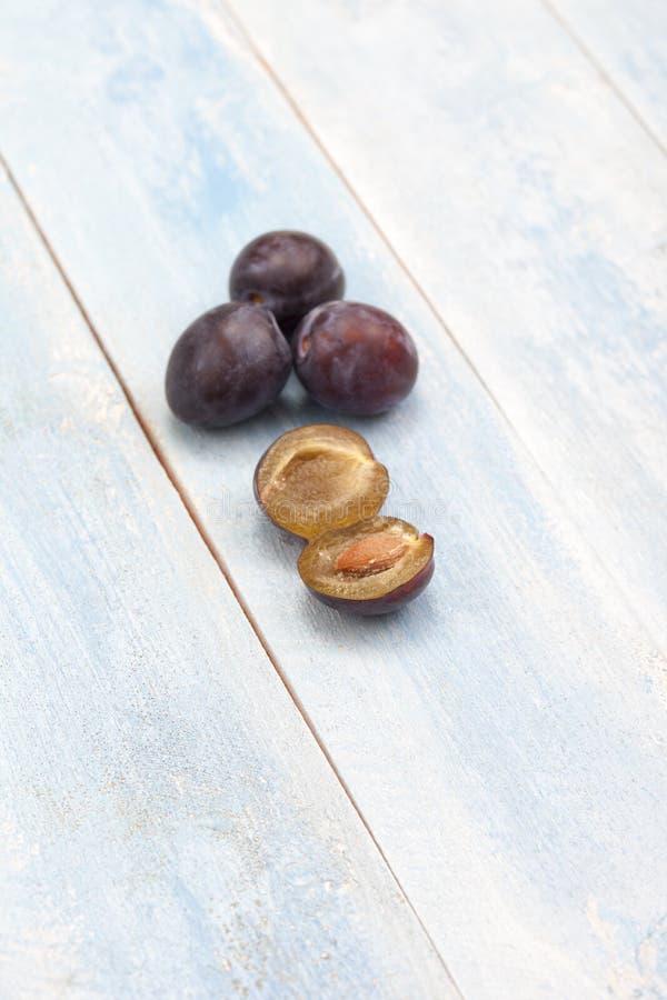Prunes sur le conseil en bois bleu photos libres de droits