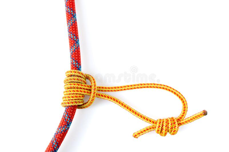 Prusik fnuren eller trefaldig glidande hake som bildas med en 5mm gul Prusik ögla runt om 9 8mm rött klättrarep arkivfoton