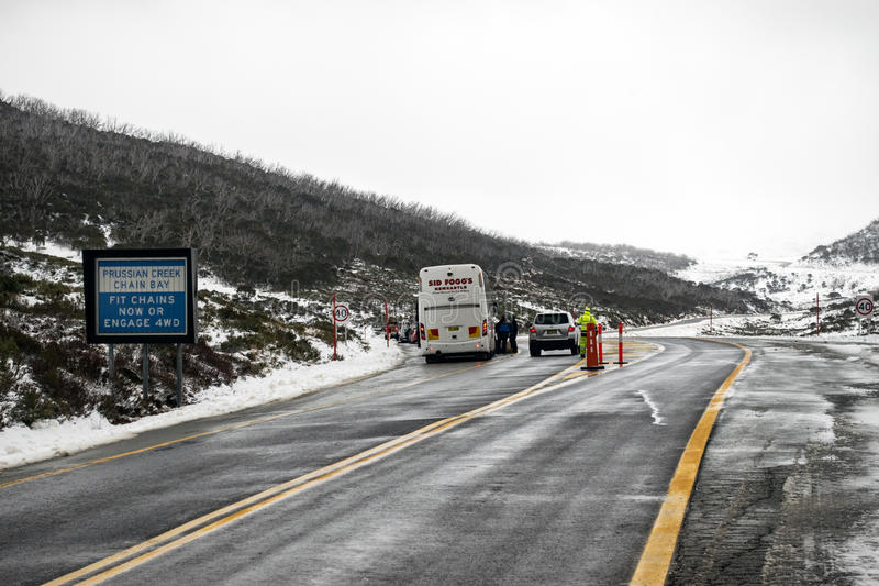 Prussian Creek chain bay being used by drivers. Perisher Valley - 23 June 2016: Prussian Creek chain bay is visited by many buses and cars stock photography