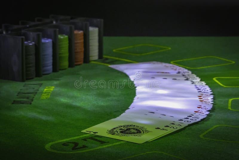 Pryda av spela kort och kasinochiper på den gröna tabellen för blackjacken som tänds med partiljus arkivfoto