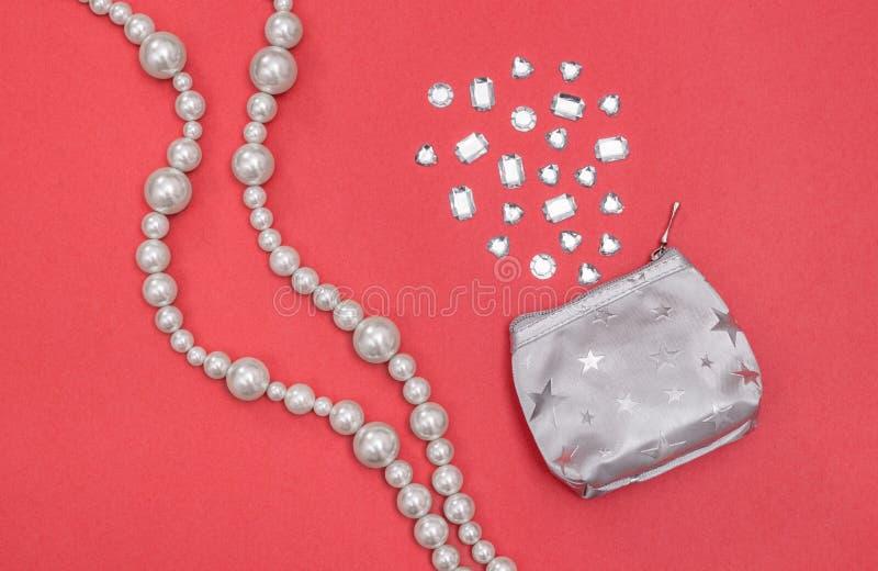 Pryda med pärlor halsbandet och försilvra handväskan med skinande ädelstenar arkivfoto