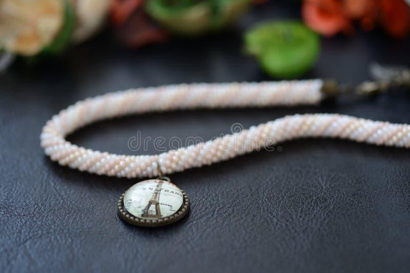 Pryda med pärlor virkningtättsittande halsbandhalsbandet med en Eiffeltornhänge fotografering för bildbyråer