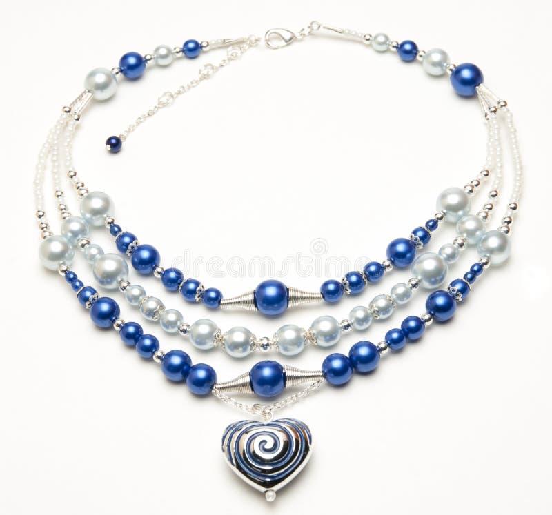 Prydd med pärlor halsband med hjärtahängen arkivbild