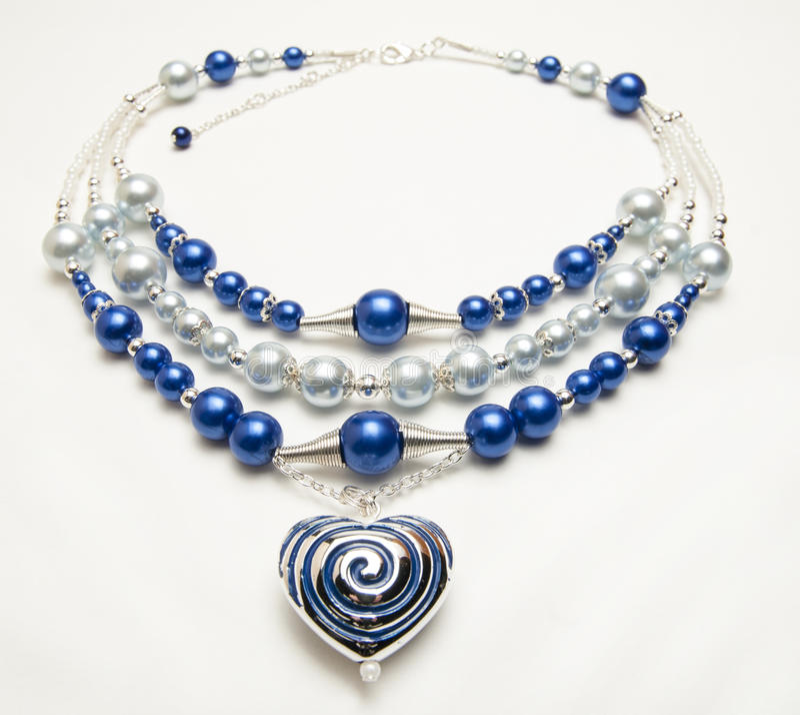 Prydd med pärlor halsband med hjärtahängen arkivfoton