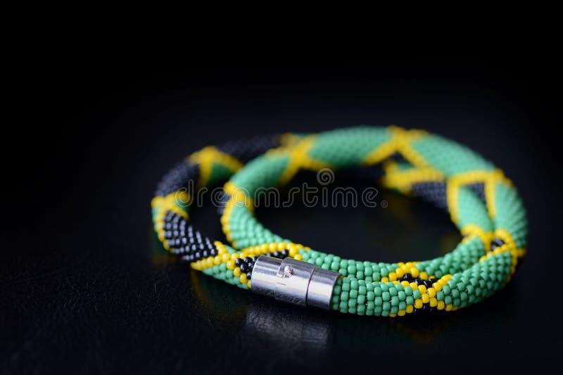 Prydd med pärlor jamaican stilhalsband på en mörk bakgrund arkivbild