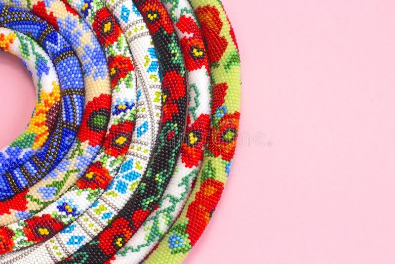 Prydde med pärlor virkninghalsband med den blom- modellen på rosa bakgrund Pryda med pärlor repet, kärna ur pärlor, fotografering för bildbyråer
