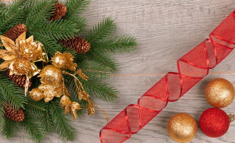 Prydlig filial för jul med kottar på en mörk bakgrund med gula och röda bollar royaltyfri foto