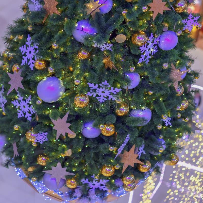 Prydligt träd för jul med garneringar, julbollar, silvergirlander, bokeh festlig bakgrund Selektivt fokusera royaltyfria foton