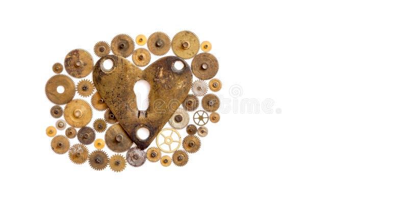 Prydnad för maskineri för förälskelsehjärtasteampunk på vit Åldrig form för bronsnyckelhålhjärta med många texturerade kuggekuggh arkivbild