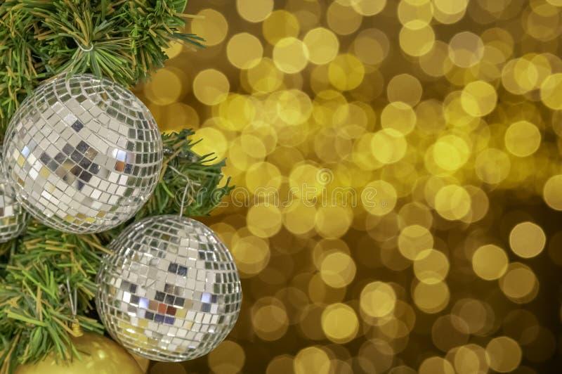 Prydnader för exponeringsglasboll på en julgran och suddiga ljus intelligens royaltyfri foto