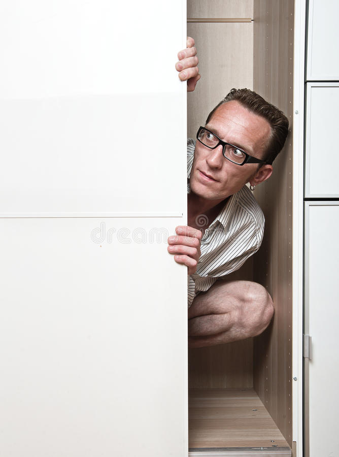 Prying man hiding inside white wardrobe. Copy space left stock photography