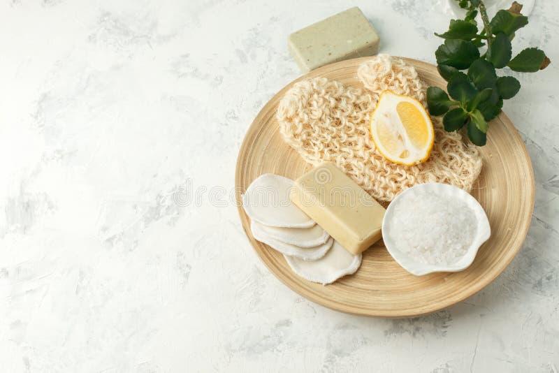Prysznic akcesoria - masuje muśnięcie, gąbka, cytryna, morze sól, mydło na lekkim tle, odgórny widok Czyścić skóra, pętaczka, obraz stock