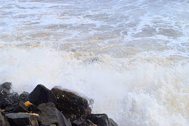 Prysznic kropli wody z rozlewaniem fali morskiej po uderzeniu skał na wybrzeżu - tło wód oceanicznych fotografia royalty free
