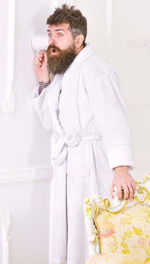 Prywatności i sekretu pojęcie Mężczyzna z brodą i wąsy podsłuchuje używać filiżankę blisko izoluje Modniś w bathrobe na zdziwiony obrazy royalty free