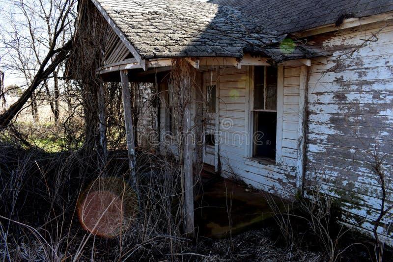 Przód stary zaniechany biały ramowy dom zdjęcie stock