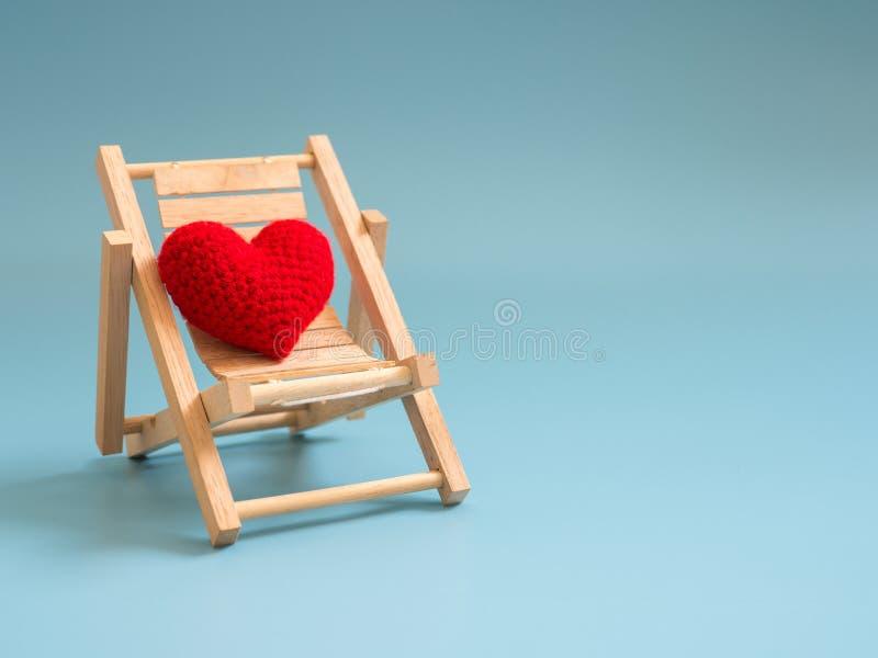 Przędzy czerwony serce na drewnianym plażowym krześle na błękitnym parawanowym tle odizolowywającym Odbitkowa przestrzeń dla teks zdjęcie royalty free