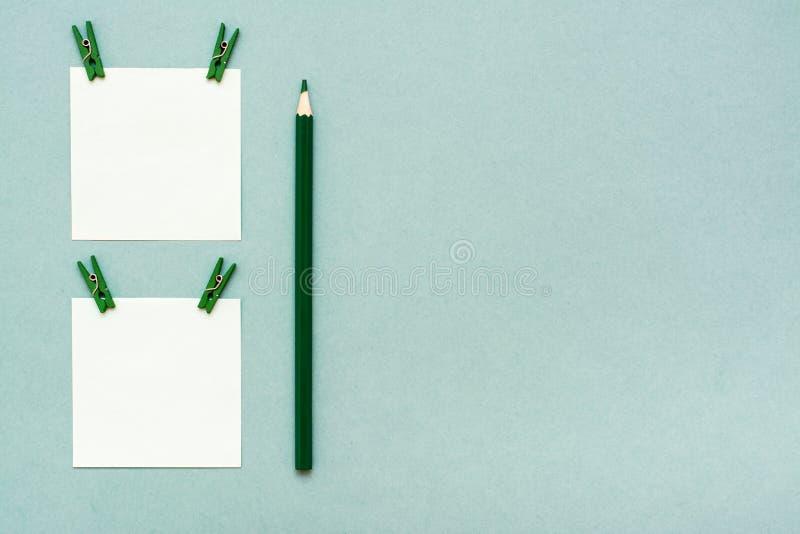 Prześcieradła dla notatek z klamerkami i ołówkiem na zielonym tle obrazy royalty free