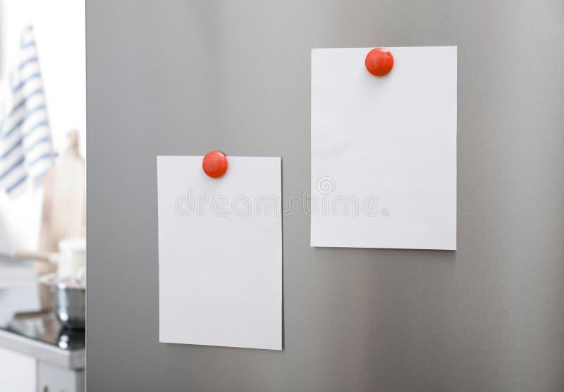 Prześcieradła papier i fotografie z magnesami na chłodziarki drzwi indoors fotografia royalty free