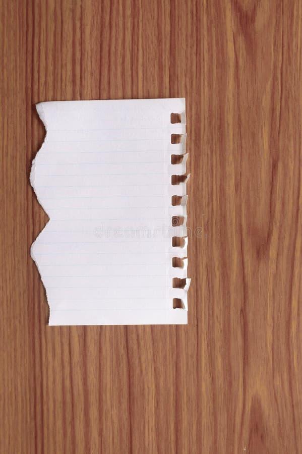 Prześcieradło notatnika papier z poszarpanym krawędzi pustym miejscem rozdzierał kawałek na odosobnionym nadmiernym drewnianym st obraz stock