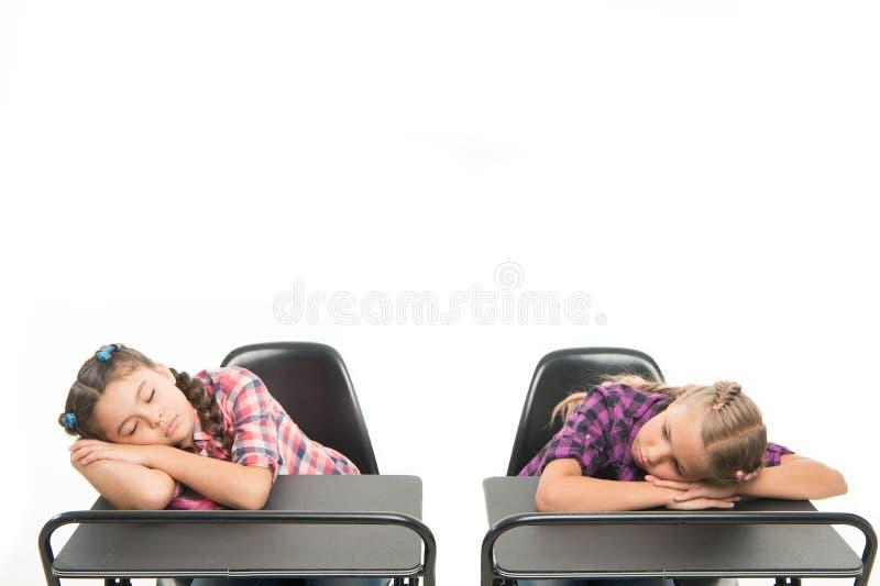 Przeżyć nudną lekcję Śliczni dzieci w wieku szkolnym śpi przy szkolnymi biurkami Małe uczennicy dostać męczyć przy lekcją wewnątr zdjęcie stock