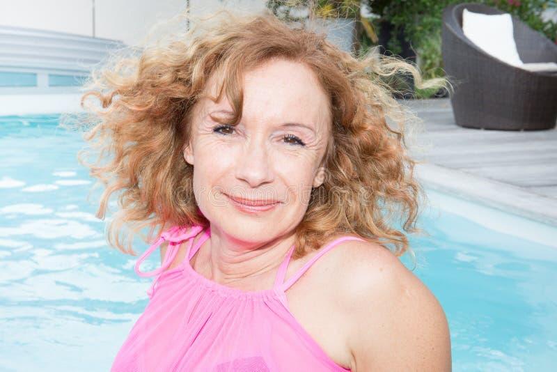 Przechodzić na emeryturę ładnej kobiety kędzierzawy senior w basenu uśmiechu obraz royalty free
