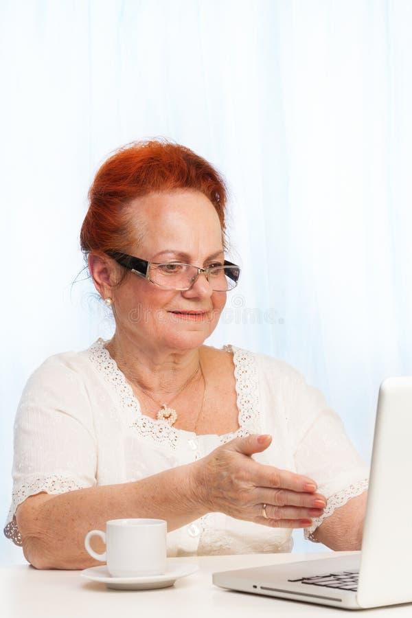 Przechodzić na emeryturę kobieta wskazuje przy laptopu ekranem zdjęcia royalty free