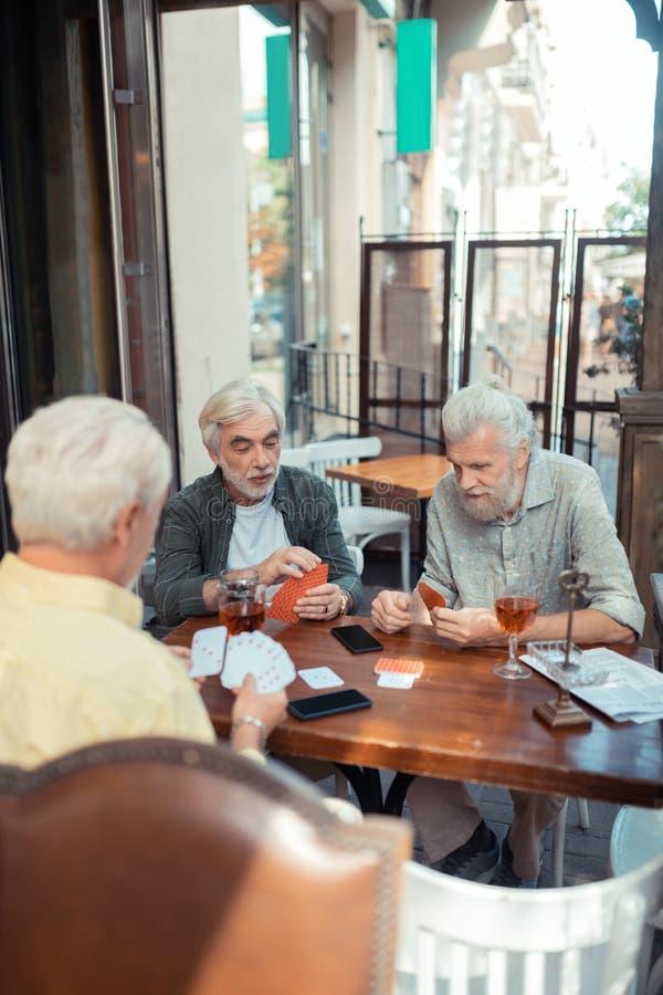 Przechodzić na emeryturę mężczyźni bawić się samochody podczas gdy siedzący na zewnątrz pubu fotografia stock