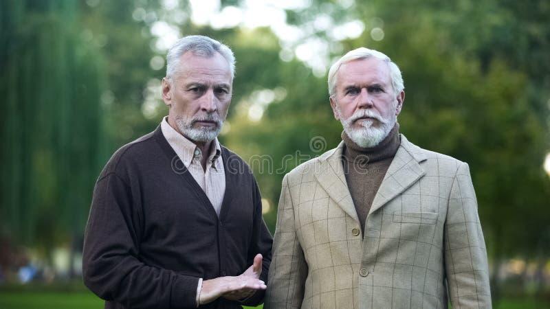 Przechodzić na emeryturę mężczyźni z przykrością patrzeje in camera, niskiej jakości utrzymanie dla emerytów obraz stock