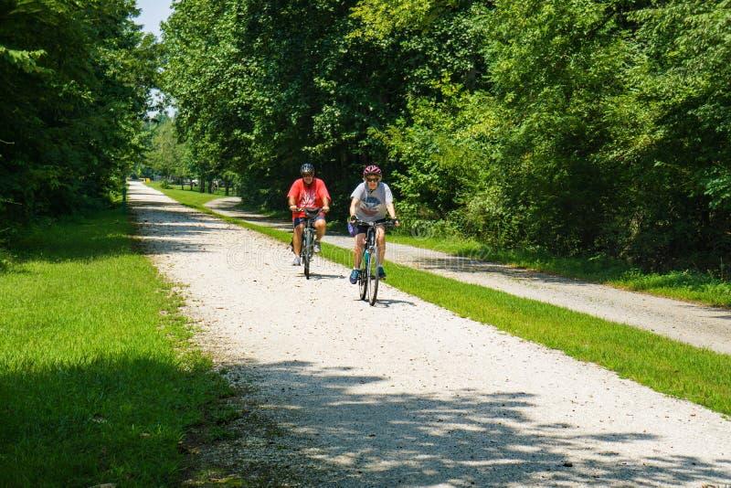 Przechodzić na emeryturę para cieszy się dzień jedzie ich bicykle na wysokość mosta śladu stanu parku lokalizować w Farmville, Cu zdjęcie stock