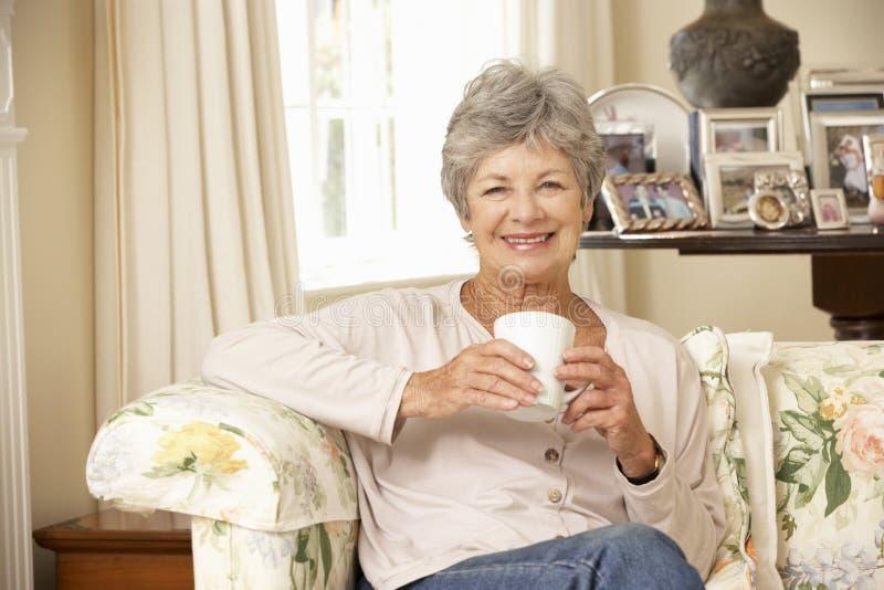 Przechodzić na emeryturę Starszy kobiety obsiadanie Na kanapie Pije herbaty W Domu fotografia royalty free