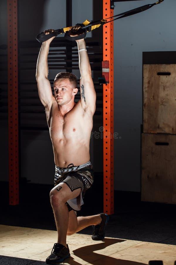 Przecinająca dysponowana sprawność fizyczna TRX pcha podnosi mężczyzna trening przy gym zdjęcie stock