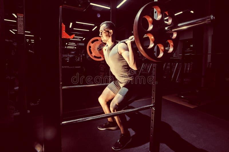 Przecinający szkolenie Część młody człowiek w sportswear podnośnym barbell obraz tonujący fotografia stock